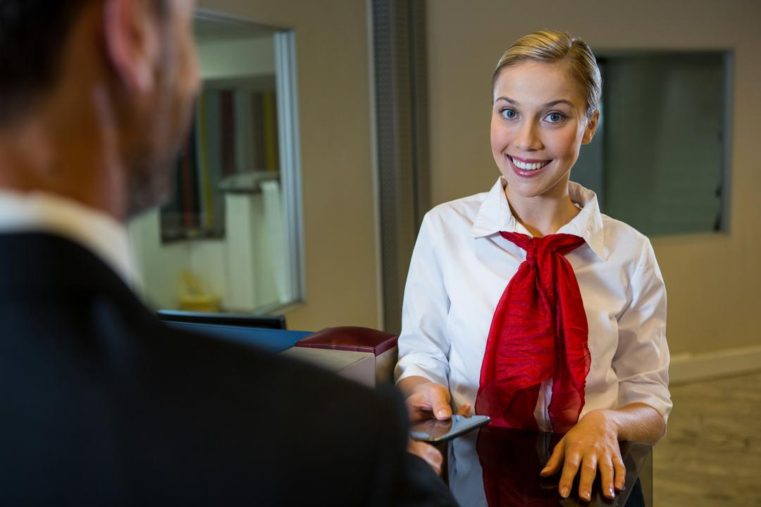 Female staff giving boarding pass to the businessman at the check in desk