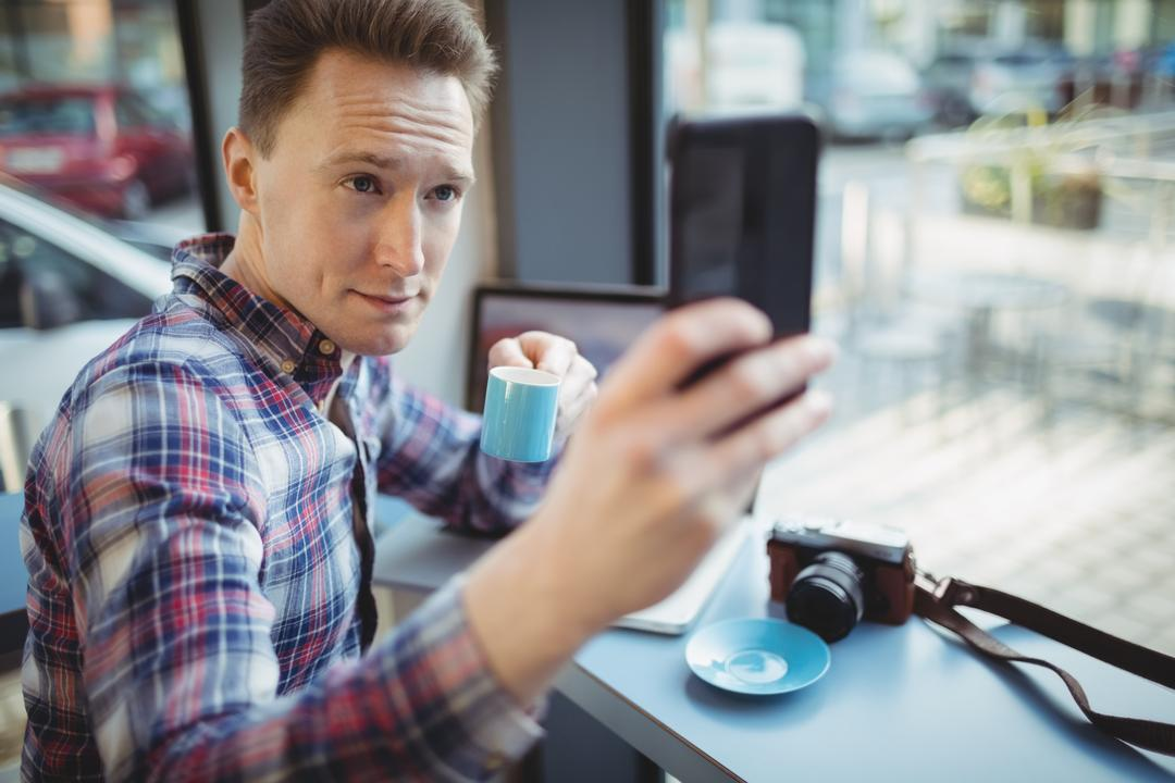 Male executive taking selfie from mobile phone in cafeteria