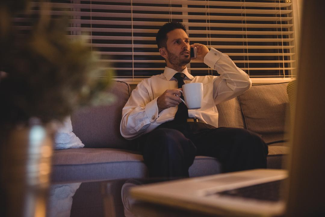 Businessman talking on mobile phone while having coffee at home
