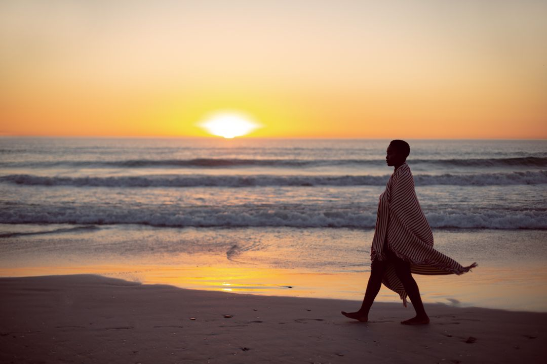 Young woman wrapped in blanket walking on the beach during sunset