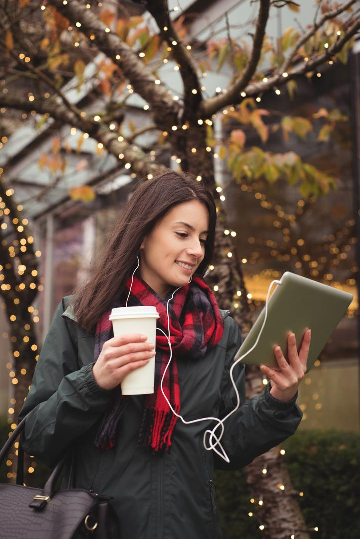 Happy woman listening music on tablet while standing by illuminated tree