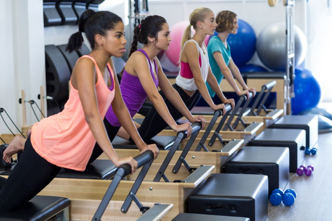 Group of women exercising on reformer in gym Free Stock Images from PikWizard
