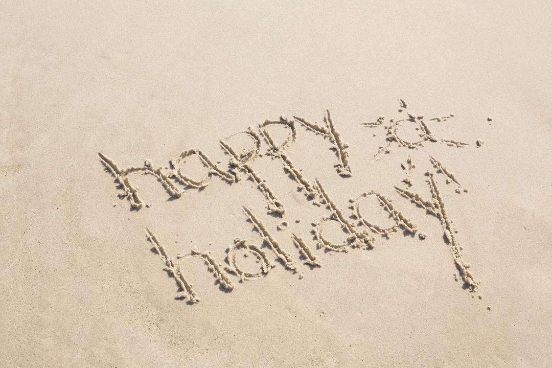 Happy holiday written on sand at beach