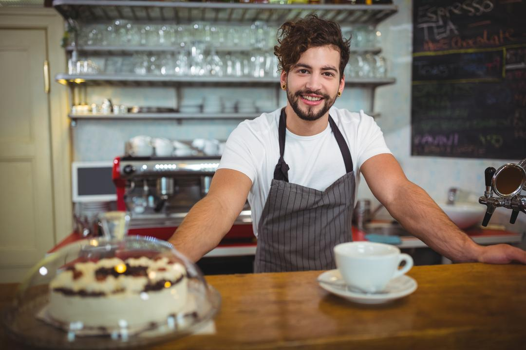 Portrait of smiling waiter standing at counter in café
