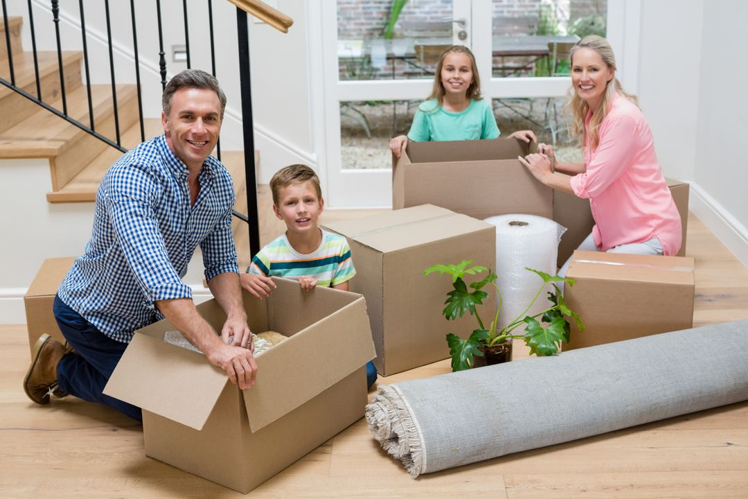 Portrait of parents and kids unpacking carton boxes in living room at new home