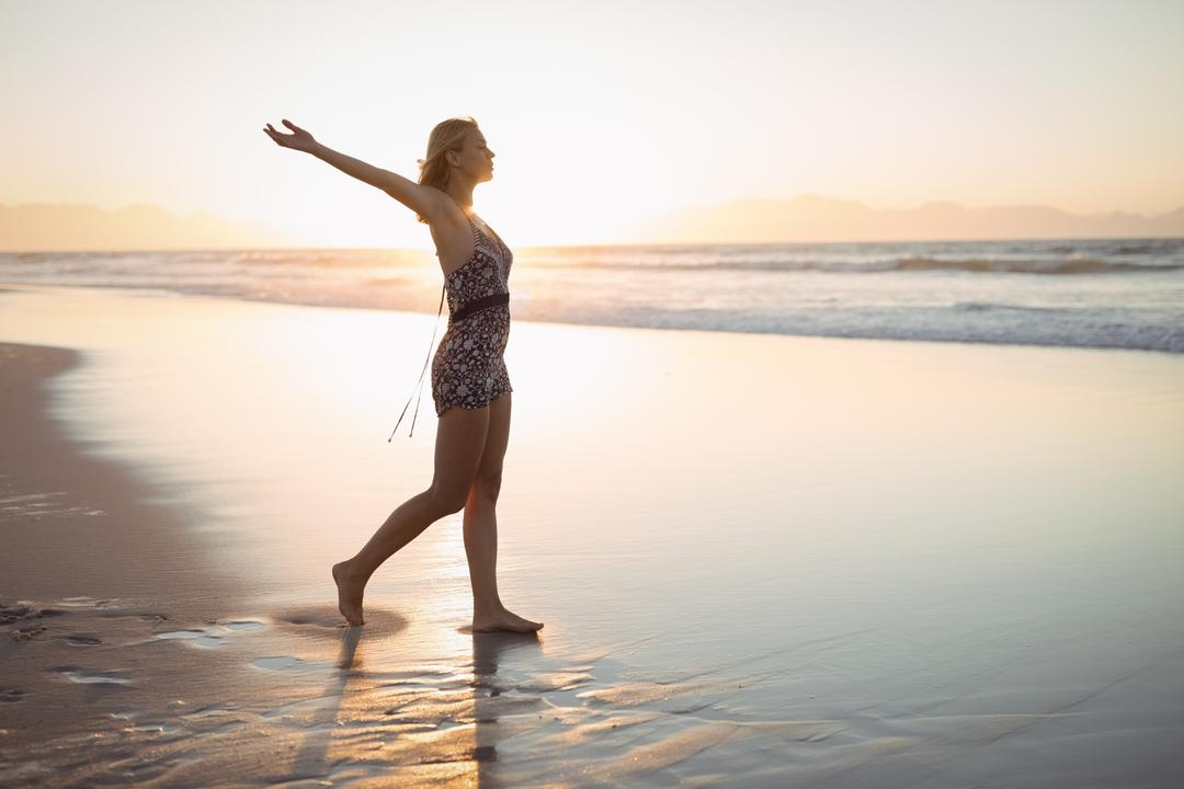 Full length side view of woman with arms outstretched standing at beach during dusk