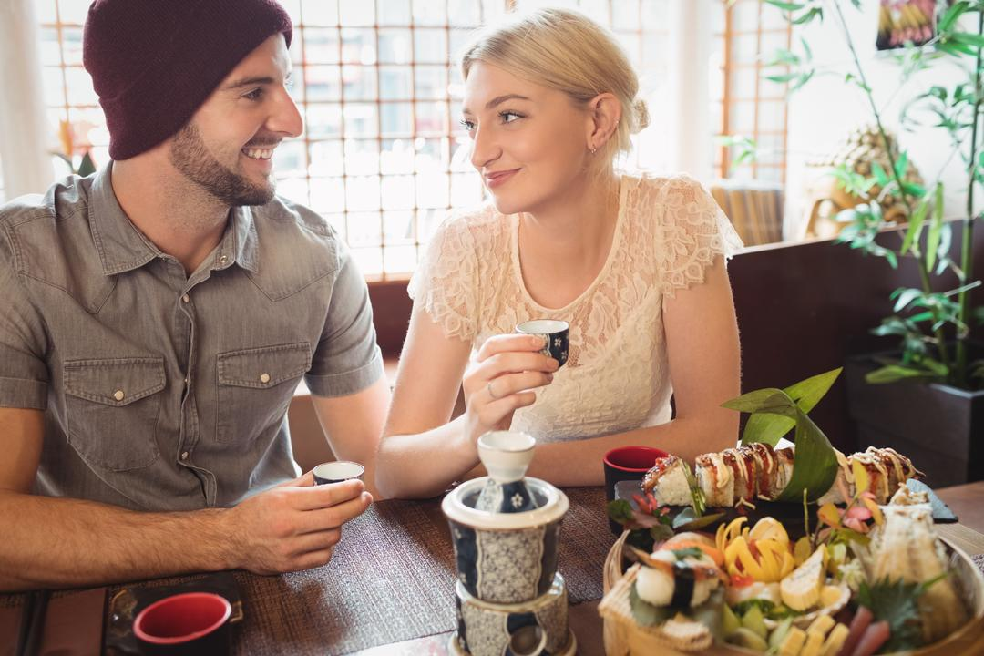 Couple interacting with each other while having tea in restaurant