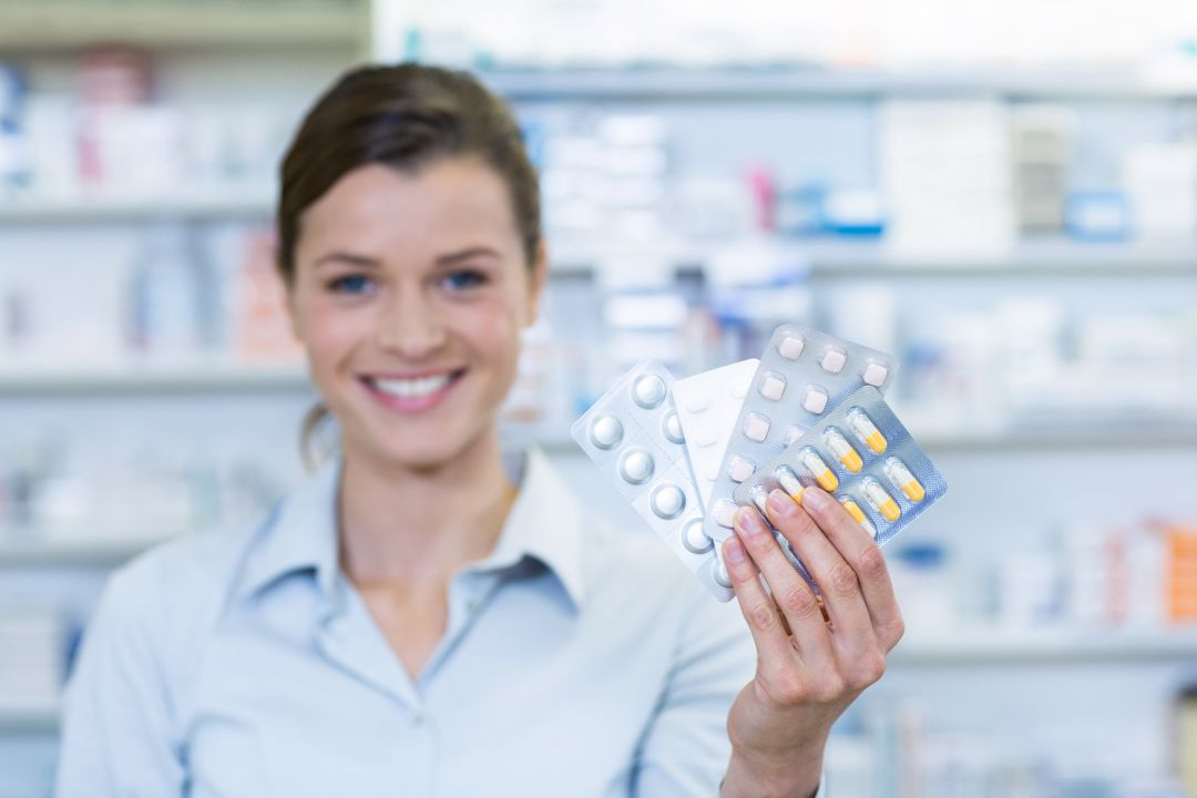 Portrait of pharmacist showing medicine in pharmacy Free Stock Images from PikWizard