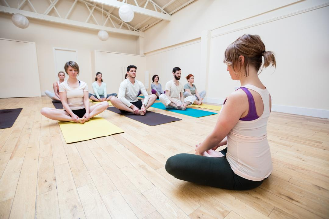 Trainer assisting group of people in meditation