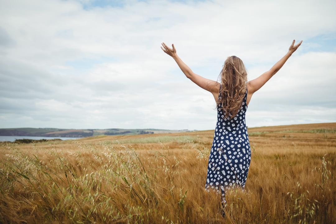 Rear view woman standing with arms outstretched in field