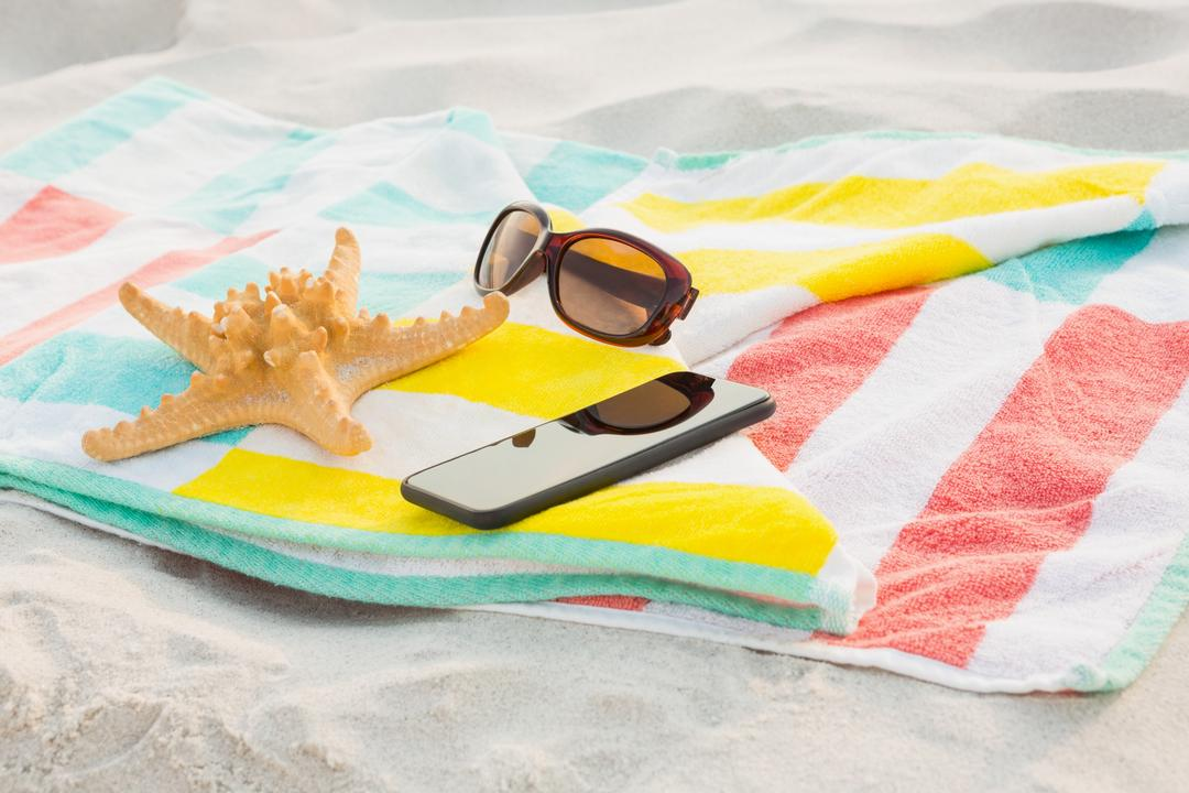 Starfish, sunglasses and mobile phone kept on beach blanket at beach Free Stock Images from PikWizard