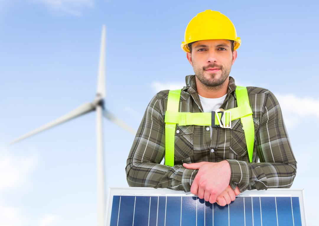Portrait of handyman standing with solar panel and wind turbine in background