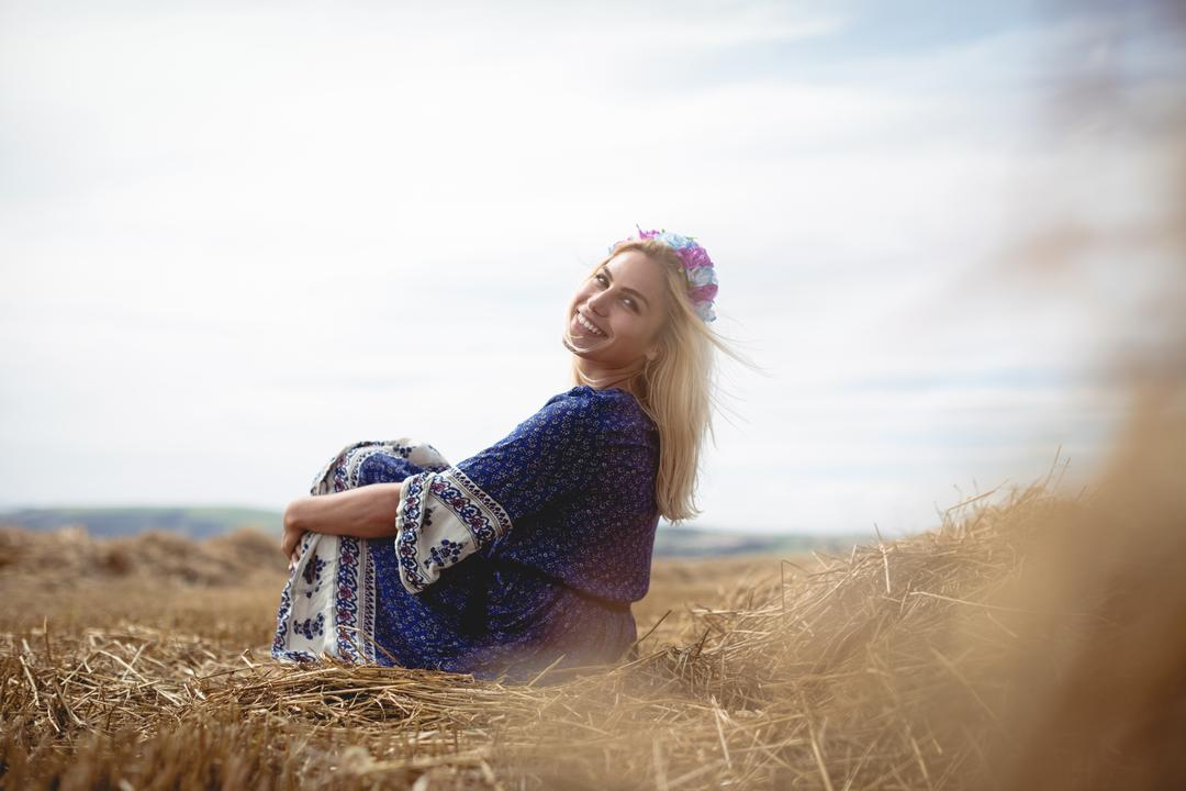 Carefree blonde woman sitting in field