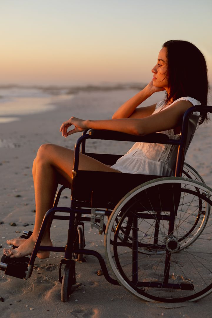 Thoughtful disabled woman in wheelchair on the beach
