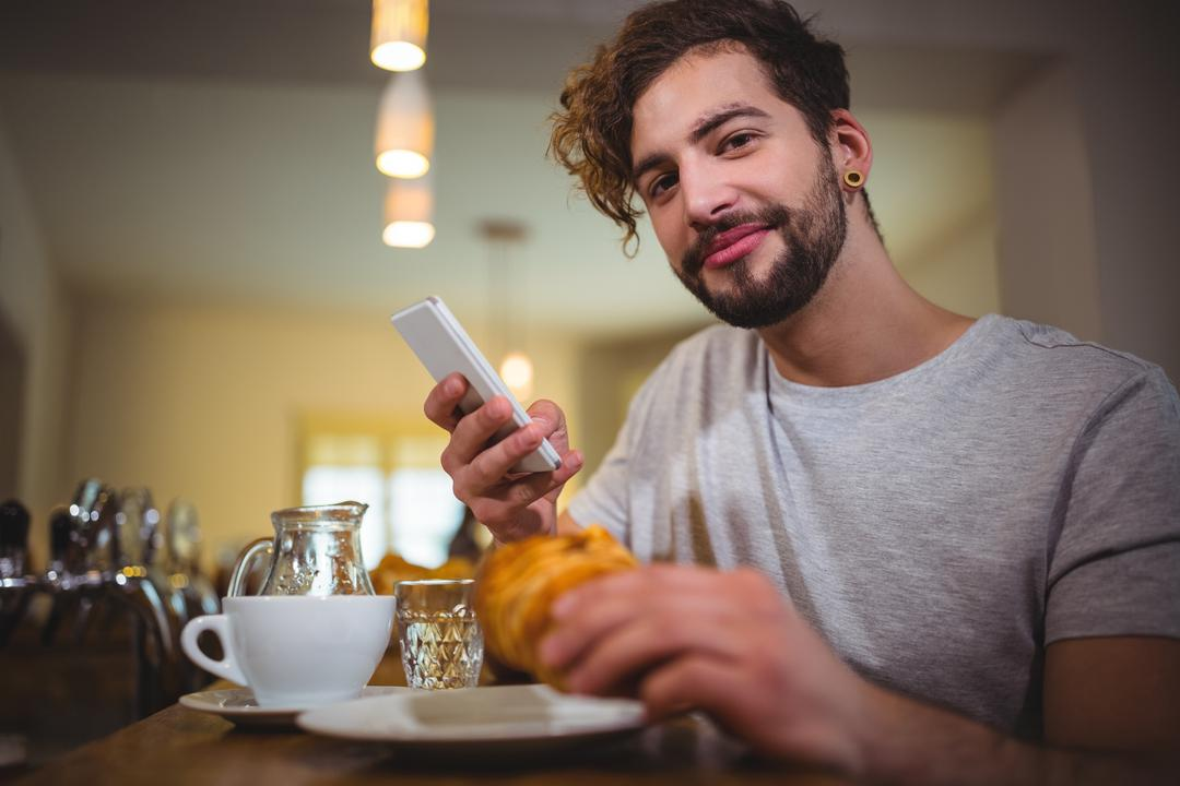 Portrait of man using mobile phone while having croissant in café
