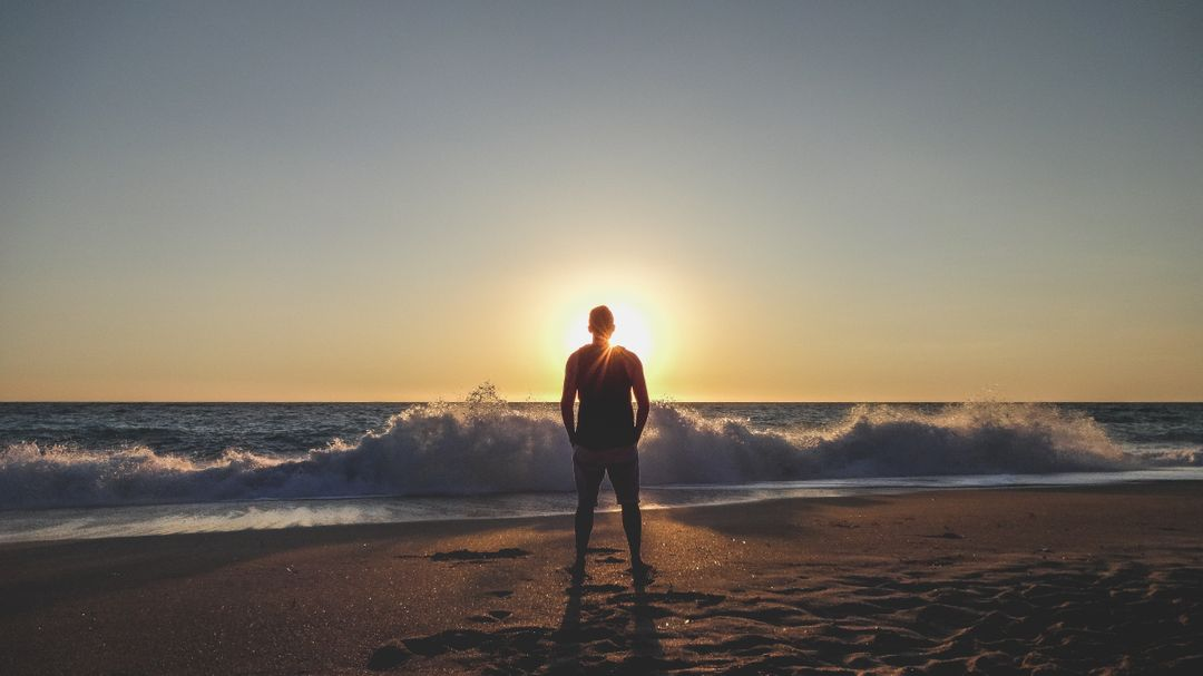 Man standing on a beach looking at the sunset
