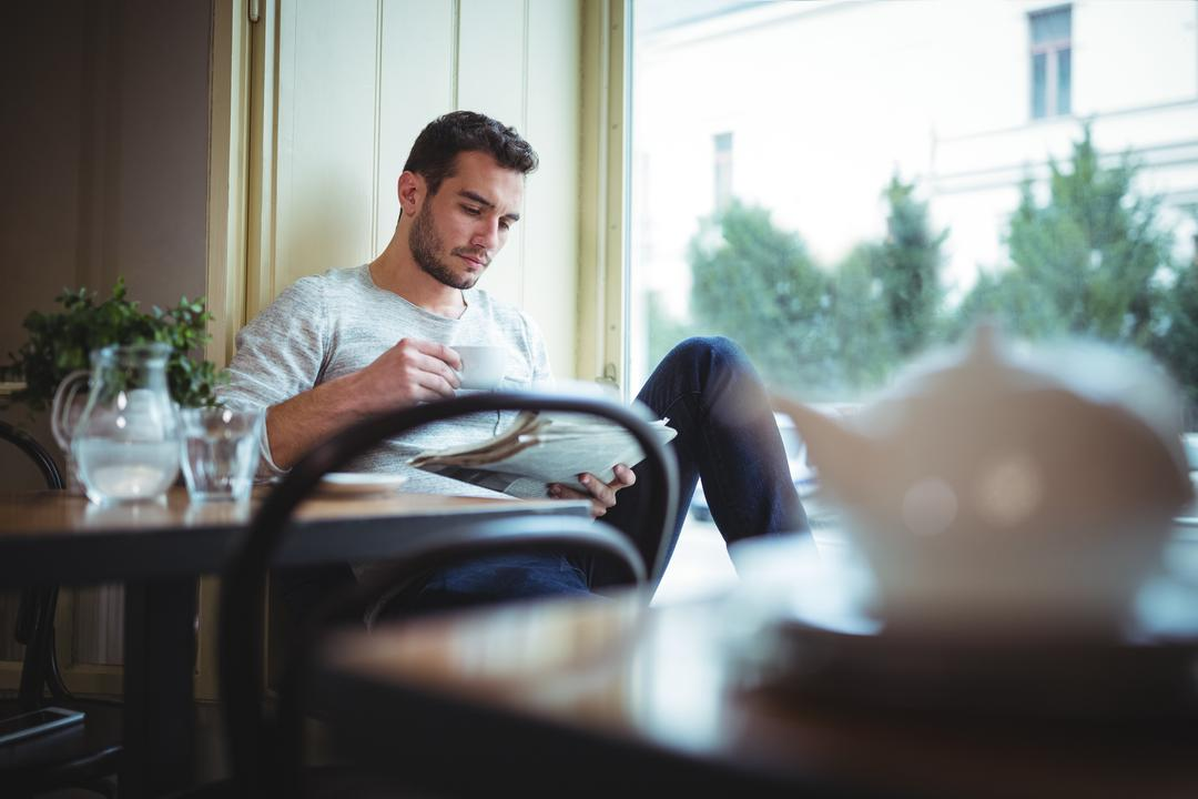 Image of a Man Reading the Newspaper and Drinking Coffee