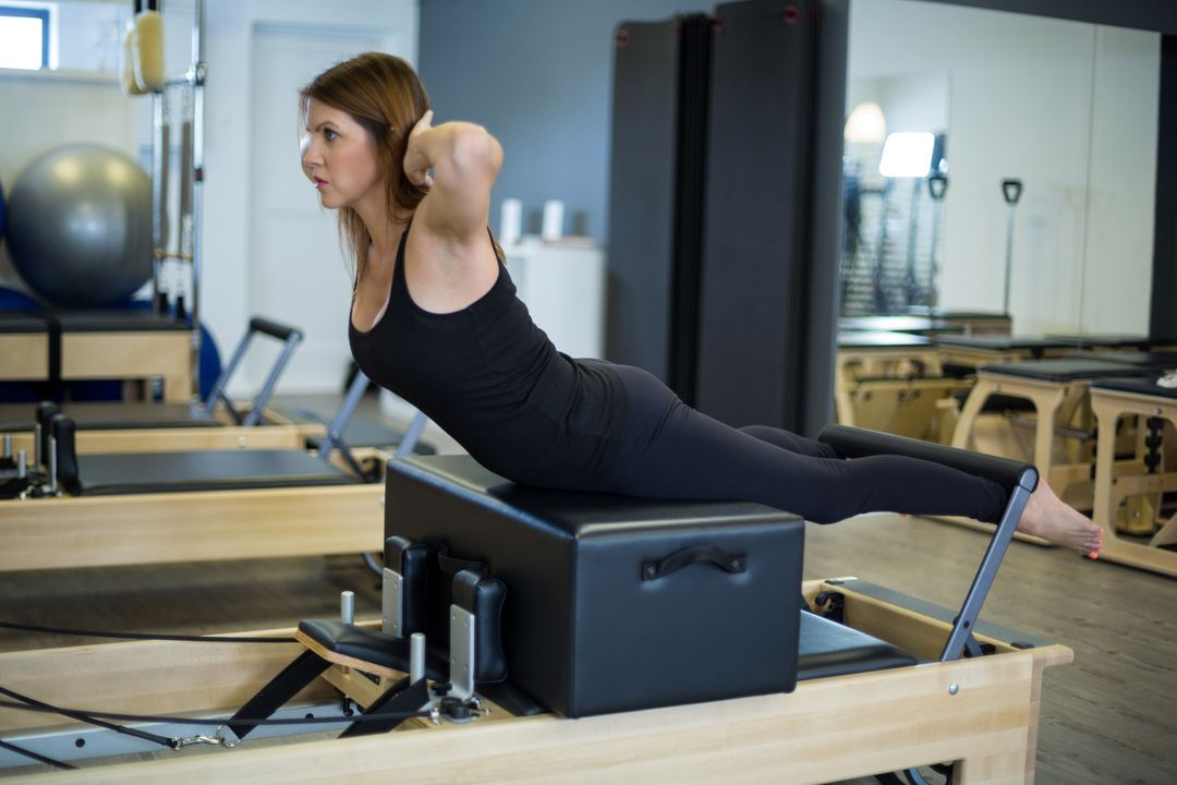 Determined woman practicing stretching exercise on reformer in gym Free Stock Images from PikWizard