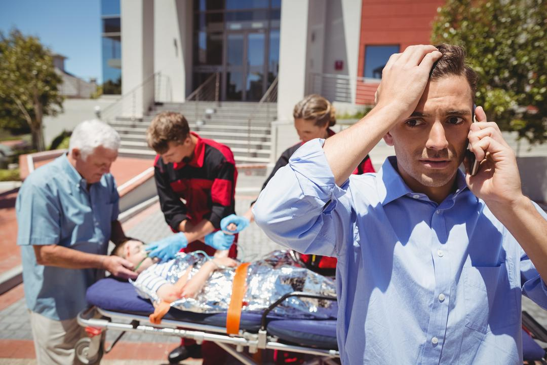 Man talking on mobile phone and paramedics examining injured boy on street in background Free Stock Images from PikWizard