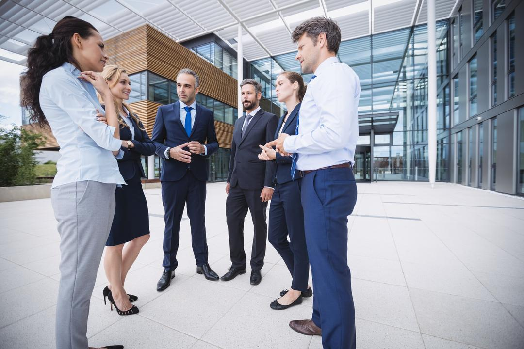 Group of cheerful businesspeople interacting outside office building