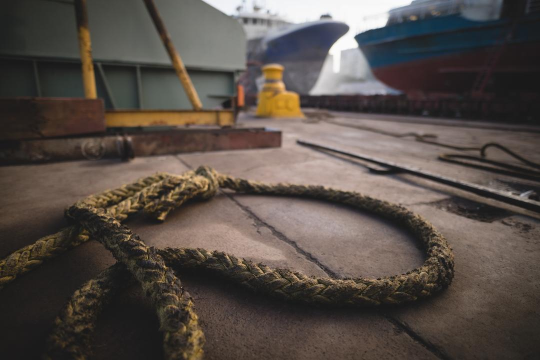 Close-up of mooring rope kept on harbor