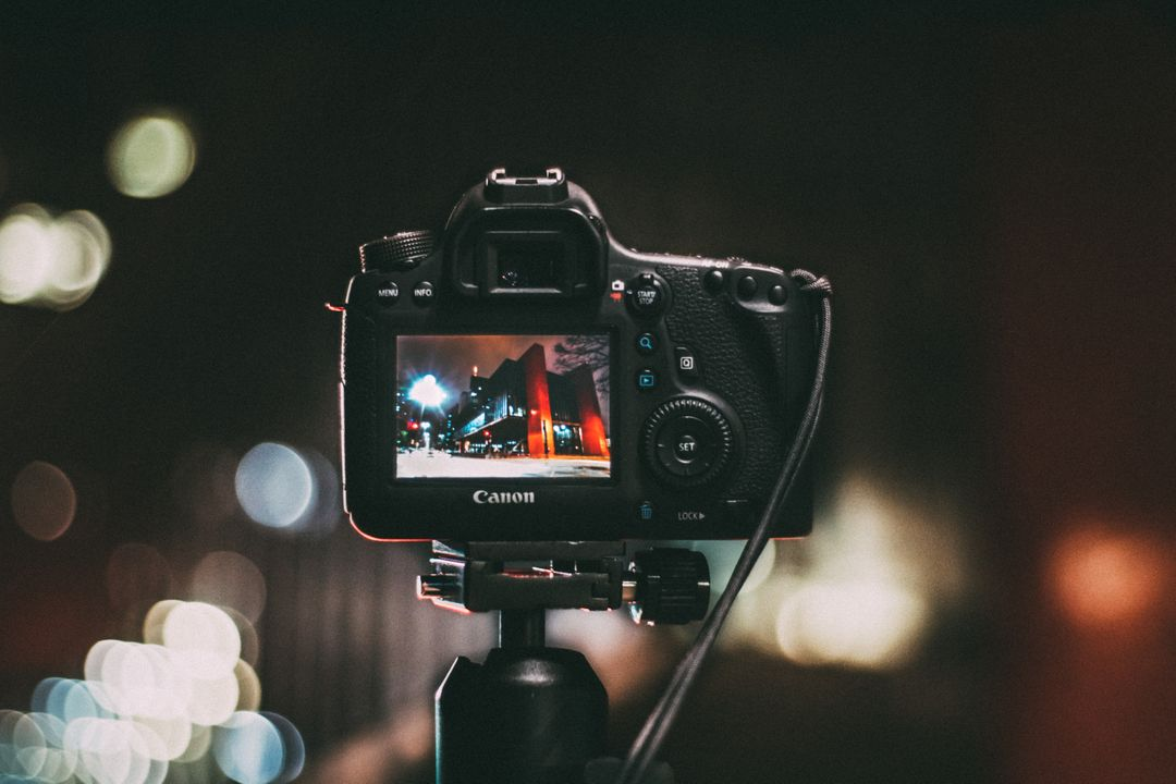 Canon camera on a tripod, taking a picture of a building at night with lights