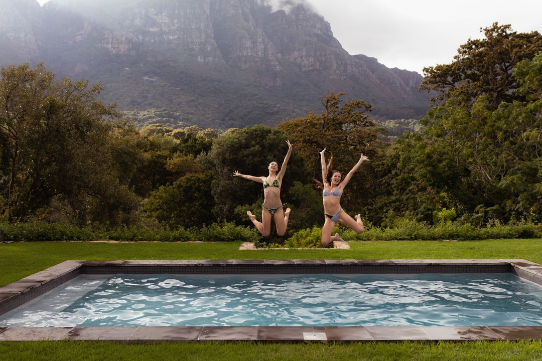 Happy female friends jumping in swimming pool at backyard