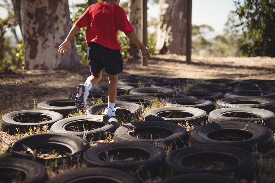 Boy running over tyres during obstacle course in boot camp Free Stock Images from PikWizard