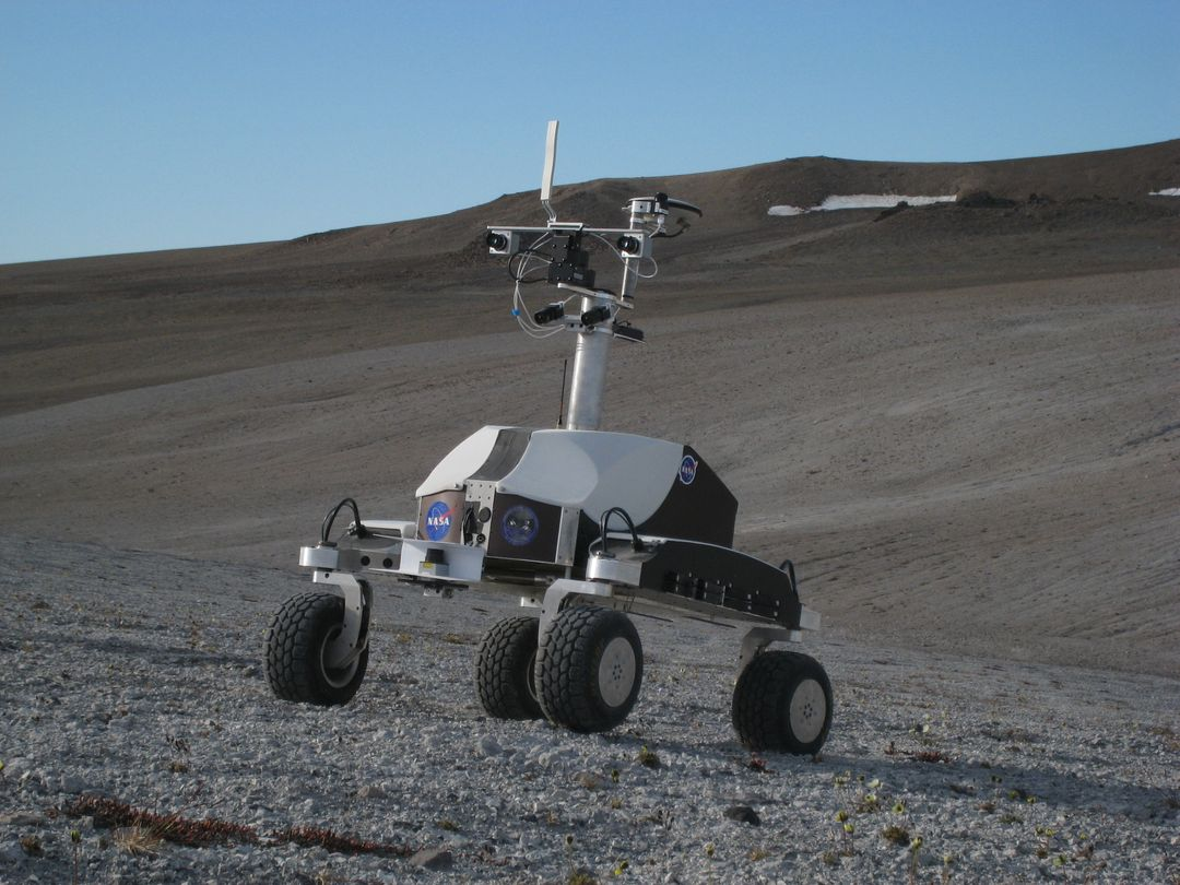 Haughton-Mars Project: - Photo credit to Matt Deans (NASA)  K-10 Rover 'Black' driving on 'Drill Hill at Haughton Creater Devon Island, Nunavut, in the Canadian high arctic. Which lies in the 'frost rubble zone' of the Earth, i.e., in a polar desert environment and is the only crater known to lie in such an environment. Beginning in 1997, the crater and its surroundings are studied as a promising Mars analog by the NASA-led Haughton-Mars Project.  (photo reference IMG_1278.JPG)