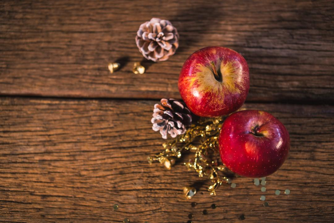 Apple and pine cone on wooden plank during christmas time
