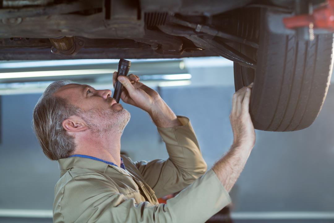 Mechanic examining car using flashlight in repair shop Free Stock Images from PikWizard