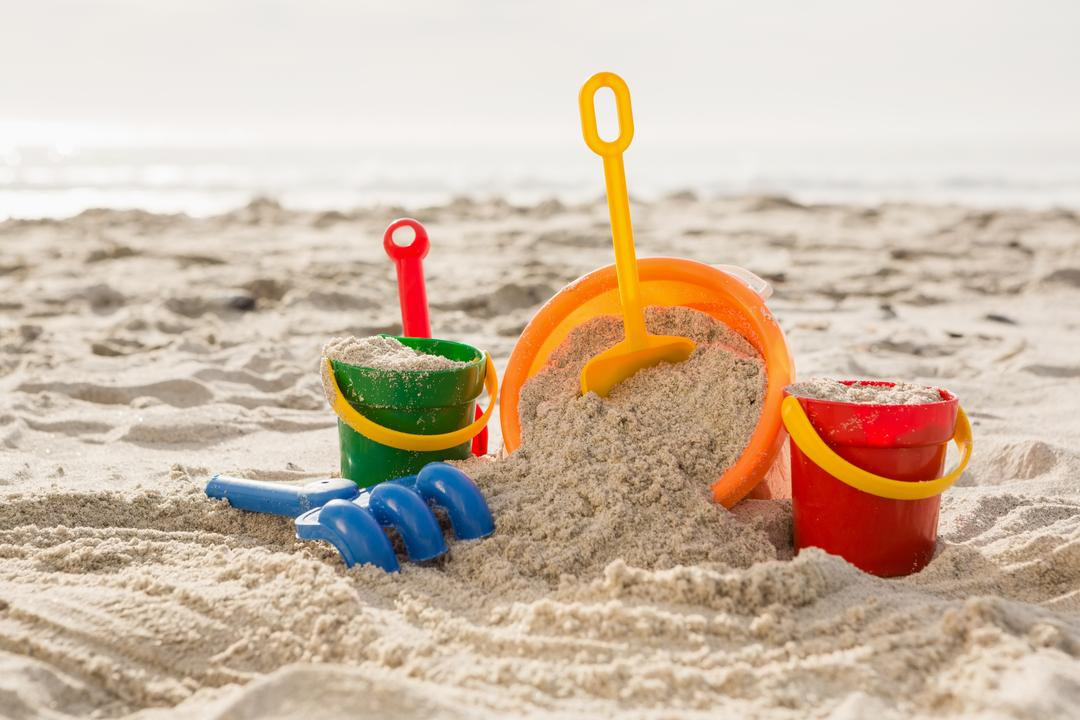 Three bucket with sand and a spade on tropical sand beach