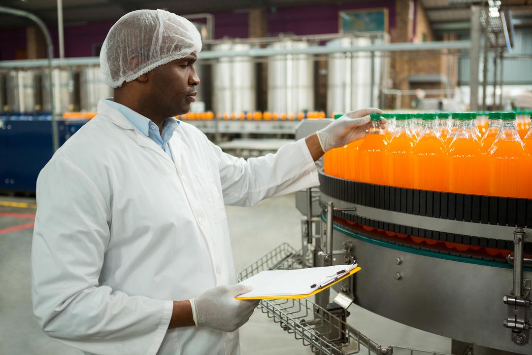 Serious male worker examining bottles in juice factory