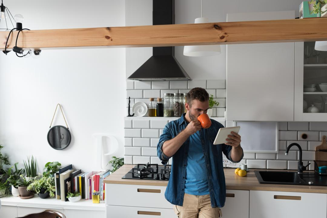 Man having coffee while using digital tablet in the kitchen at home