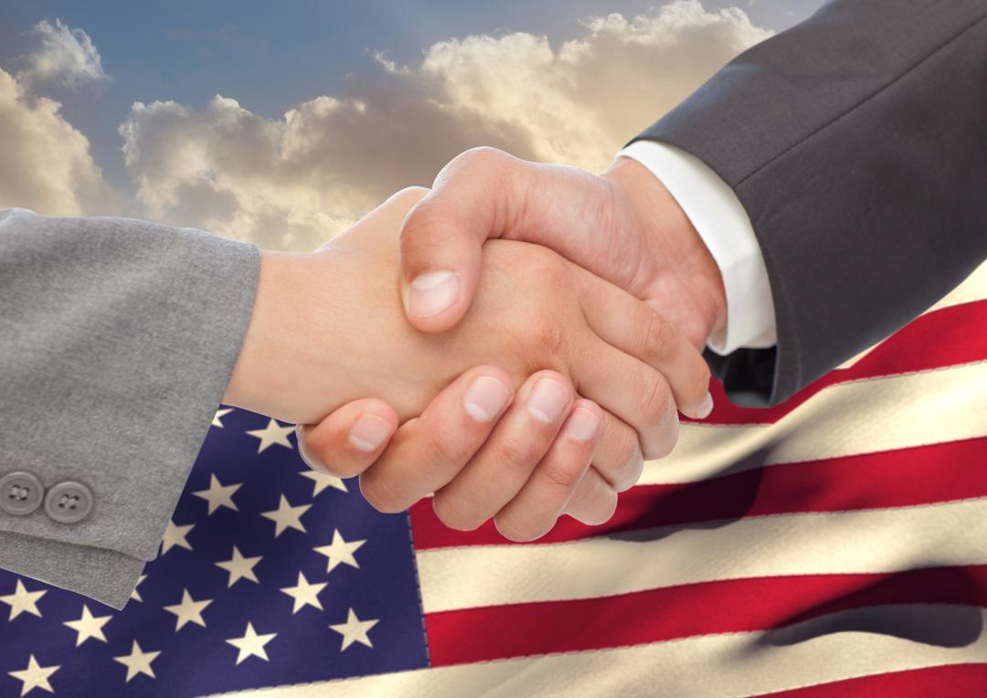 Digital composite image of businesspeople shaking hands against american flag