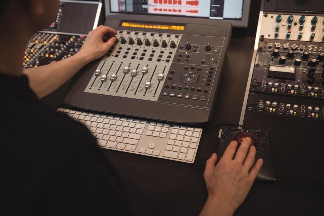 Audio engineer using sound mixer in recording studio