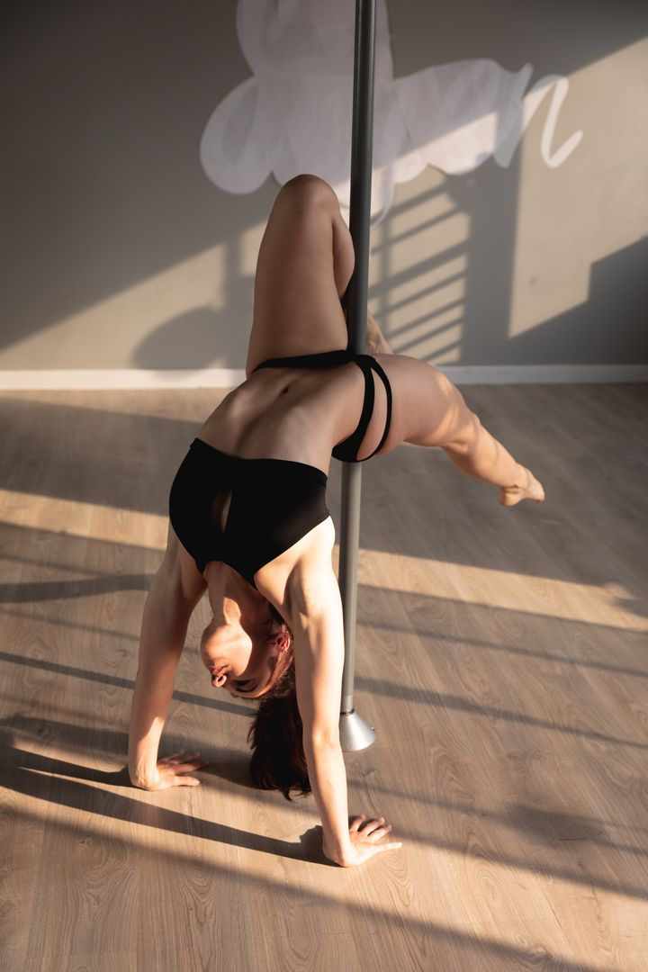 A fit attractive Caucasian woman enjoying pole dance training at a studio, doing handstand with one leg resting on the pole and the other leg stretched Free Stock Images from PikWizard