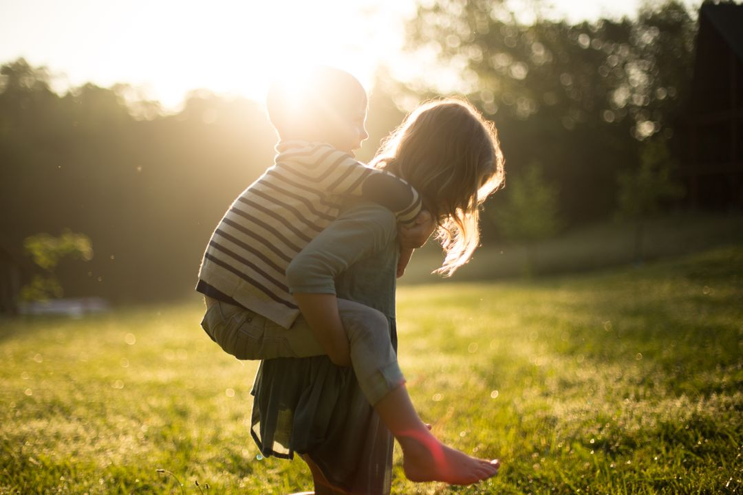Image of a mother holding her son on her back in a garden with the sun shining in the background