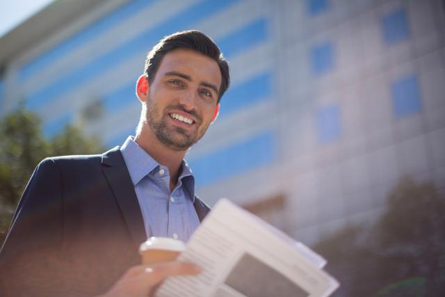Portrait of smiling businessman holding newspaper and coffee cup near office building