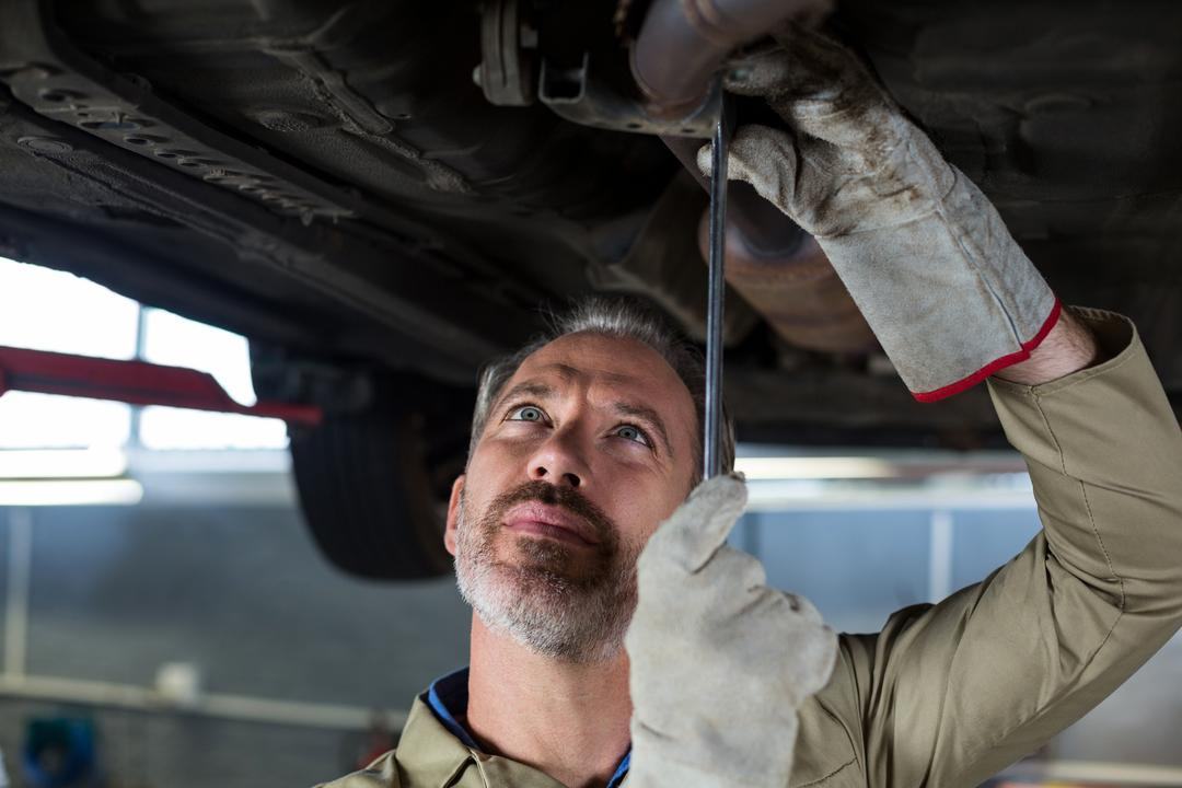 Mechanic servicing a car in repair shop Free Stock Images from PikWizard