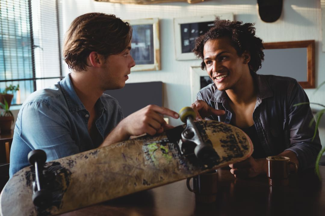 two friends chatting with skateboard on table
