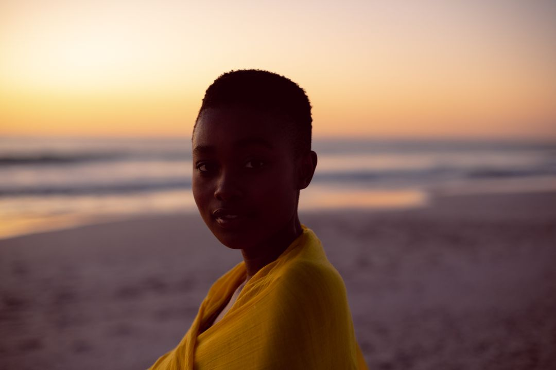 Portrait of young woman wrapped in yellow scarf on the beach