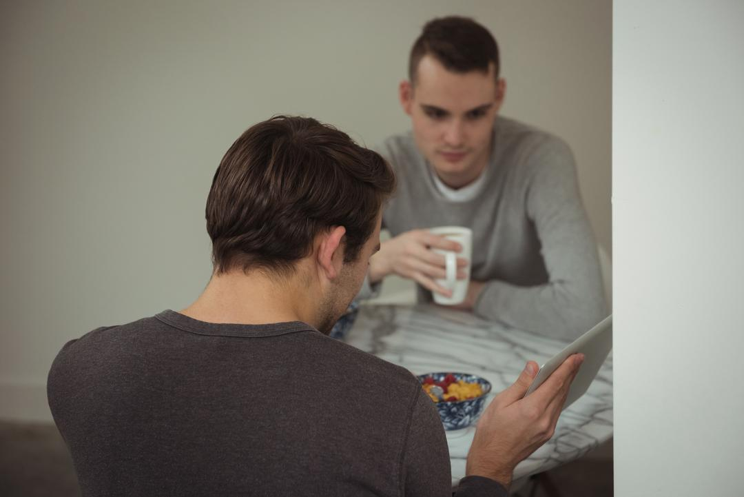 Gay couple looking at digital tablet while having breakfast at home Free Stock Images from PikWizard