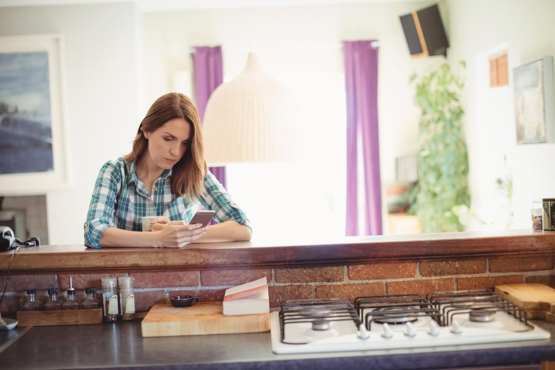 Woman using mobile phone while having coffee in kitchen at home