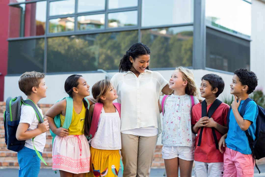 Cheerful female teacher with children standing outside school Free Stock Images from PikWizard
