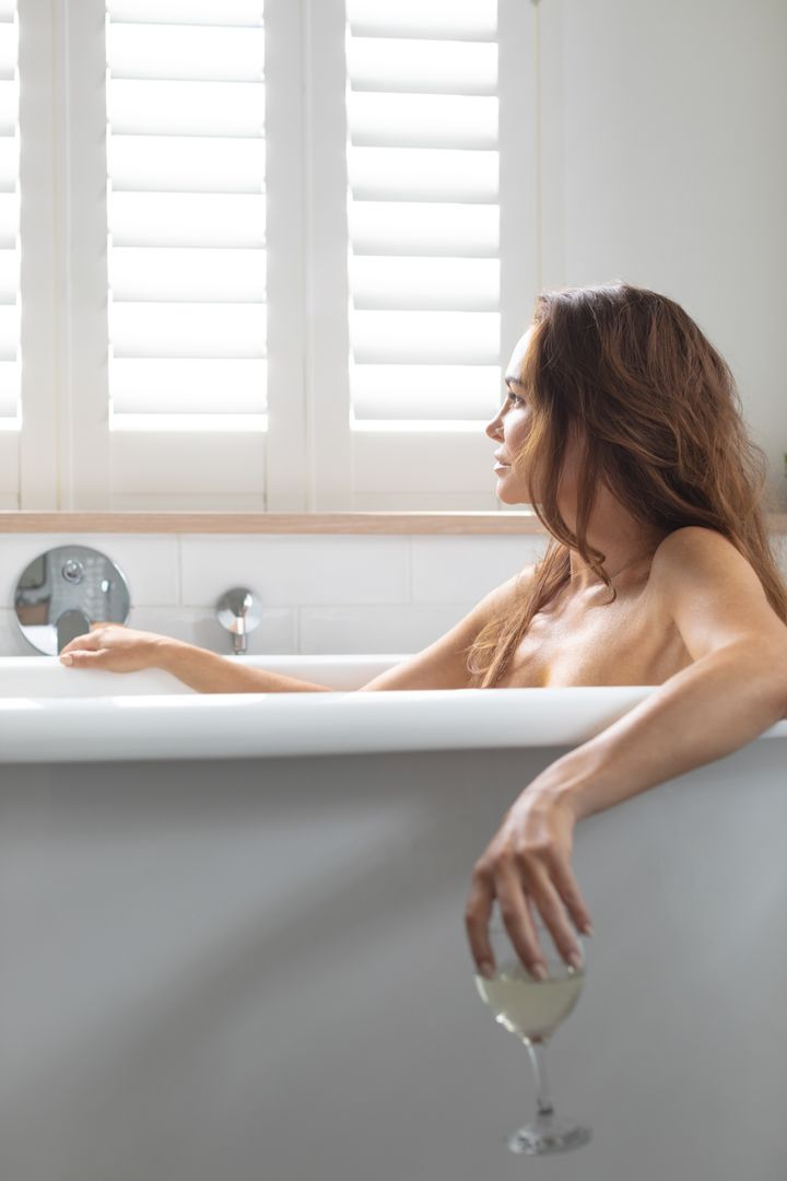 Beautiful woman having champagne while relaxing in bathtub at bathroom