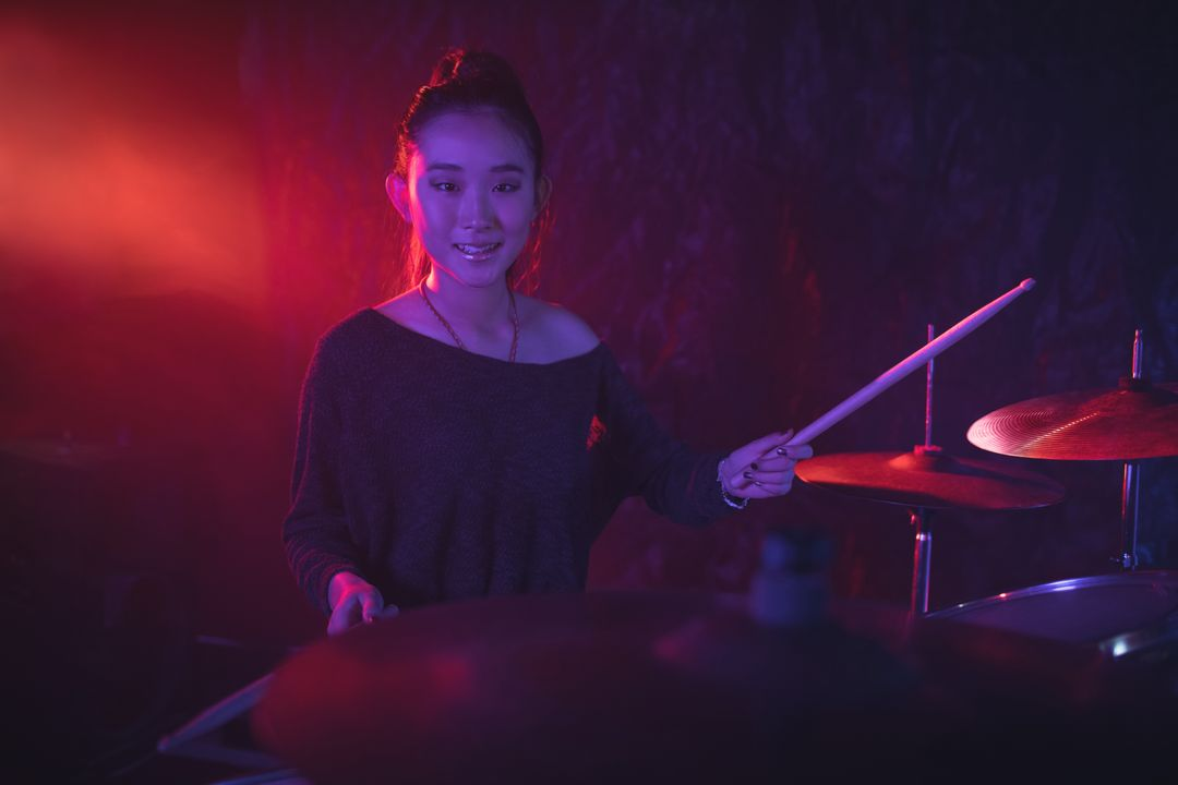 Portrait of smiling female drummer playing drum kit in illuminated nightclub Free Stock Images from PikWizard