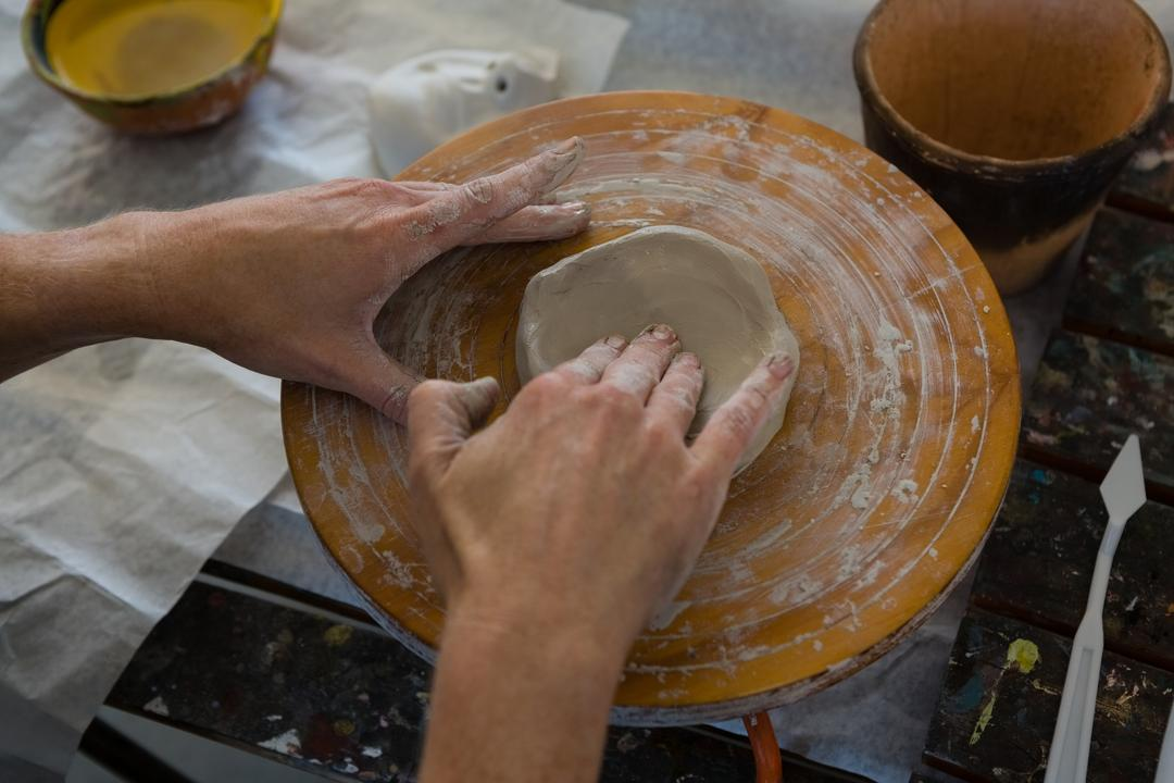 Cropped hand of craftsperson making clay product on pottery wheel in art class Free Stock Images from PikWizard