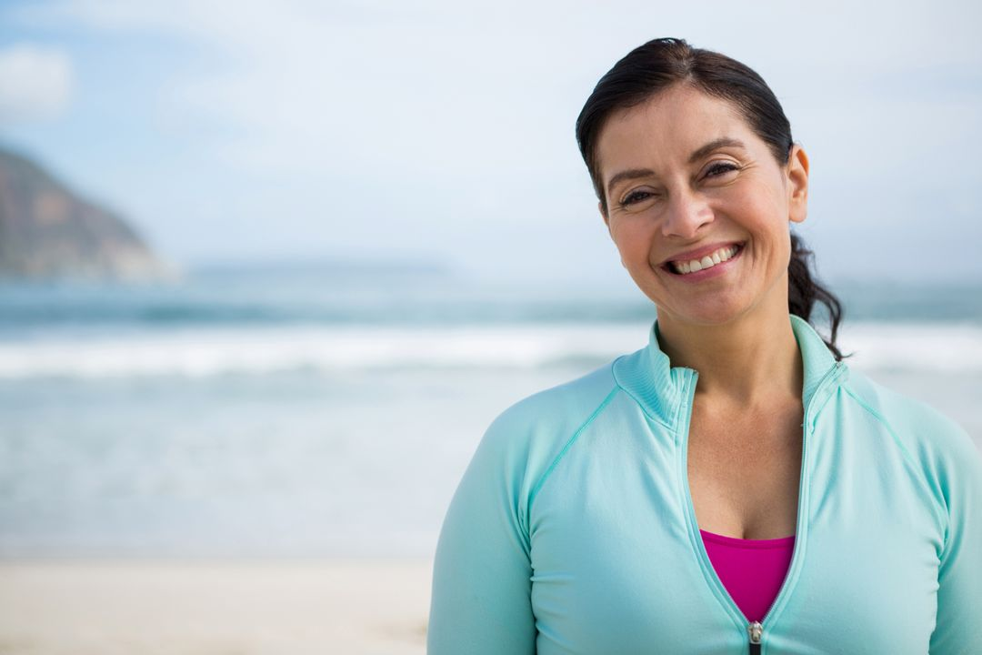 Portrait of smiling woman on beach during winter Free Stock Images from PikWizard