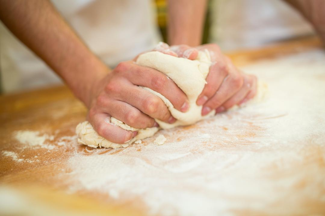 Close-up of bakers hands kneading dough on counter